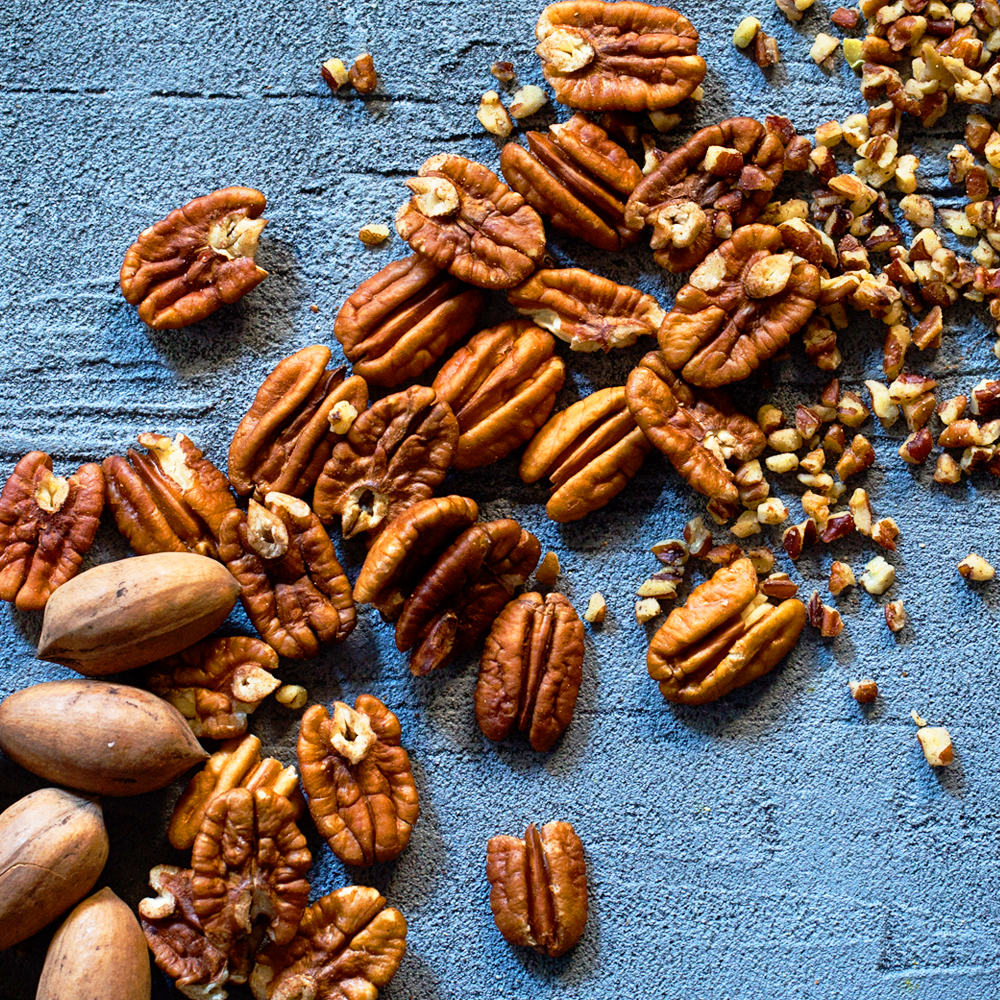 Pecans from shell to pieces laid artfully on a counter. USDA's CFAP 2 will provide direct assistance to pecan growers impacted by the pandemic.