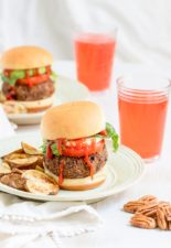 Fully dressed, Black Bean Pecan Burgers sit on plates with homemade fries next to glasses of juice.